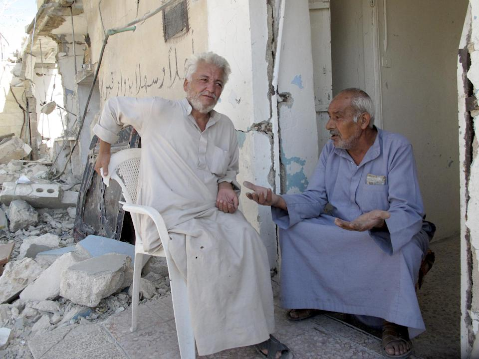 Syrians Bassem Kharfani, left, and Mahmoud Jikar sit at the door of Jikar's house, one of more than a dozen homes destroyed in a Syrian government bombing last week that killed more than 40 people, in Azaz, Syria, on Monday, Aug. 20, 2012. (AP Photo/Ben Hubbard)