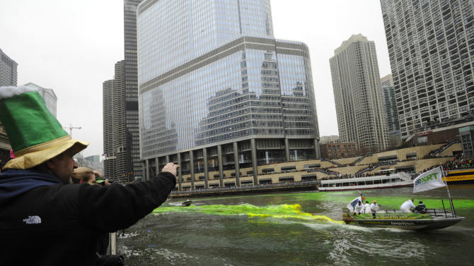 Bystanders look on as the Chicago River is dyed green ahead of the St. Patrick's Day parade in Chicago, Saturday, March, 16, 2013.  With the holiday itself falling on a Sunday, many celebrations were scheduled instead for Saturday because of religious observances. (AP Photo/Paul Beaty)