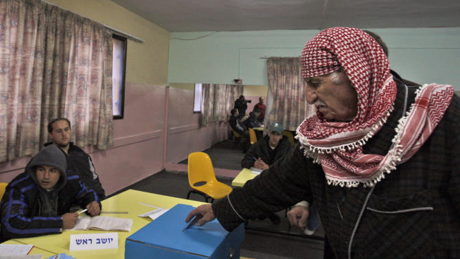 FILE - In this Tuesday, Feb. 10, 2009 file photo an elderly Israeli Arab man, right, casts his ballot in a polling station in the northern Israeli city of Nazareth. Israeli Arab activist Rasool Saada, unseen, is crisscrossing the country to encourage fellow Arab citizens to vote in Jan. 22 parliamentary elections, convinced they can make a difference. Numerically, he's right. Historically, it hasn't worked out that way. Arabs make up about a fifth of Israel's population, but their voter turnout has been much lower than that of the Jewish majority. Many Arabs are disillusioned with politics, feeling alienated as a minority in a Jewish state and dissatisfied with their own squabbling, ineffective representatives. (AP Photo/Muhammed Muheisen, File)