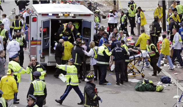 Medical workers aid injured people at the finish line of the 2013 Boston Marathon in Boston, Monday, April 15, 2013. Two bombs exploded near the finish line of the Boston Marathon on Monday, killing a