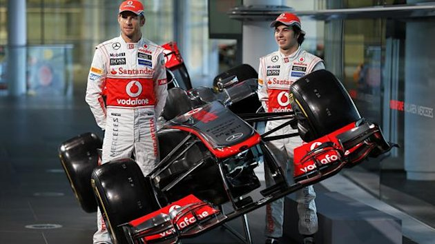 McLaren Formula One drivers Jenson Button of Britain (L) and Sergio Perez of Mexico pose for photographers after unveiling the McLaren MP4-28 car at the company's headquarters in Woking, southern England January 31, 2013 (Reuters)