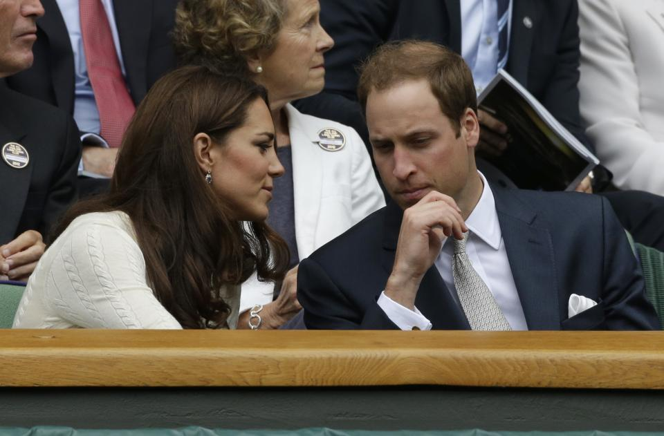 Britain's Prince William, right, and his wife Kate, Duchess of Cambridge speak to each other ahead of a quarterfinals match between Roger Federer of Switzerland and Mikhail Youzhny of Russia at the All England Lawn Tennis Championships at Wimbledon, England, Wednesday July 4, 2012. (AP Photo/Anja Niedringhaus)