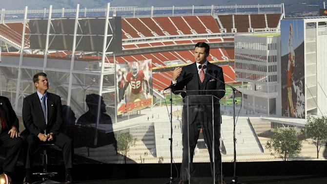 San Francisco 49ers head coach Jim Harbaugh, left, listens as team owner Jed York speaks at a groundbreaking ceremony at the construction site for the 49ers' new NFL football stadium in Santa Clara, Calif., Thursday, April 19, 2012. (AP Photo/Jeff Chiu)