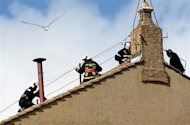 A seagull flies as members of the fire and rescue service set a chimney on the roof of the Sistine Chapel at the Vatican March 9, 2013. REUTERS/Dylan Martinez