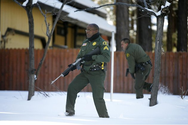 San Bernardino County Sheriff's officers Ken Owens, center, and Bernabe Ortiz search a home for former Los Angeles police officer Christopher Dorner in Big Bear Lake, Calif, Sunday, Feb. 10, 2013. The