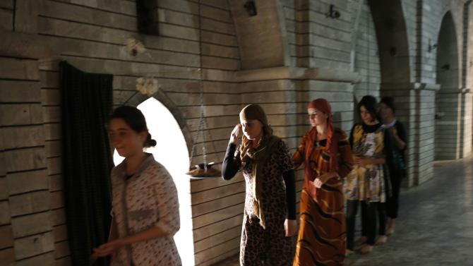 Displaced girls from the minority Yazidi sect, who fled violence in the Iraqi town of Sinjar, worship at their main holy temple Lalish in Shikhan