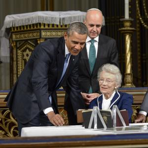 U.S. President Barack Obama, left, Swedish Prime Minister Fredrik Reinfeldt and Nina Lagergren, right, sister of Swedish diplomat Raoul Wallenberg, view Wallenberg's Swedish passport and samples of the many thousands of protective passports Wallenberg issued to Jews in Nazi-occupied Hungary in 1944-45 at a ceremony in Stockholm's synagogue Wednesday Sept. 4, 2013. (AP Photo/Claudio Bresciani) SWEDEN OUT