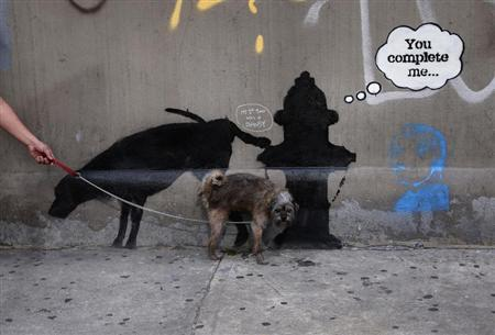 A dog urinates on a new work by British graffiti artist Bansky on West 24th street in New York City