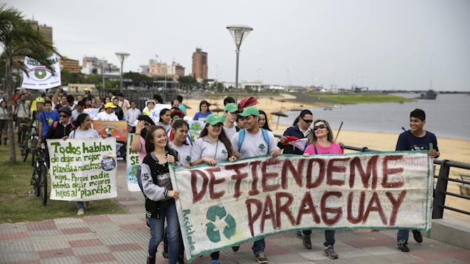 Protesters hold placards and banners during a rally ahead of the 2015 Paris Climate Change Conference, known as the COP21 summit, in Asuncion