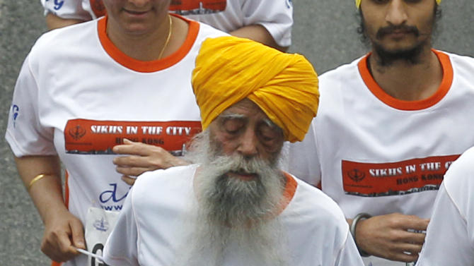 Centenarian marathon runner Fauja Singh, 101, originally from Beas Pind, in Jalandhar, India but who now lives in London, runs in a 10-kilometer race, part of the annual Hong Kong Marathon, in Hong Kong Sunday, Feb. 24, 2013. Singh will retire from public racing after competing in the marathon.  (AP Photo/Kin Cheung)