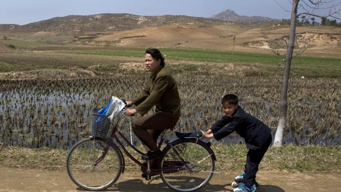 A North Korean boy on rollerblades is pulled by a woman on a bicycle on Wednesday, April 24, 2013 on a road south of Kaesong, North Korea, and north of the demilitarized zone which separates the two Koreas. (AP Photo/David Guttenfelder)