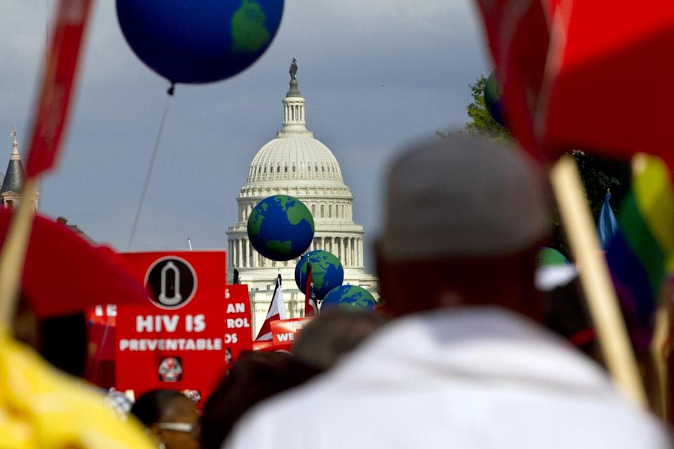 People hold signs and balloons as they participate in the AIDS March in Washington, Sunday, July 22, 2012. (AP Photo/Jacquelyn Martin)