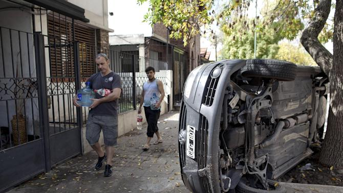 Men carry water past a car that flipped on its side during flooding in La Plata, in Argentina's Buenos Aires province, Thursday, April 4, 2013. Buenos Aires Gov. Daniel Scioli says 49 people died in this flooded capital of Argentina's largest province as torrential rains swamped entire neighborhoods, washing away cars and flooding some houses to their rooftops. The overall death toll is now 55, and more than 20 people are missing. (AP Photo/Natacha Pisarenko)