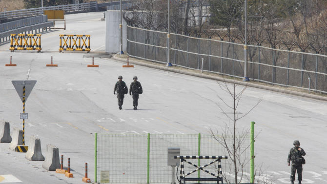 South Korean army soldiers walk on the empty road after South Korean vehicles which were refused for entry to North Korea at the customs, immigration and quarantine office in Paju, South Korea, near the border village of Panmunjom, Wednesday, April 3, 2013. North Korea on Wednesday barred South Korean workers from entering a jointly run factory park just over the heavily armed border in the North, officials in Seoul said, a day after Pyongyang announced it would restart its long-shuttered plutonium reactor and increase production of nuclear weapons material.(AP Photo/Ahn Young-joon)