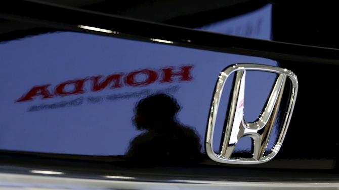 File photo of a visitor and a logo of Honda Motor reflected on a Honda Odyssey car at the company showroom in Tokyo