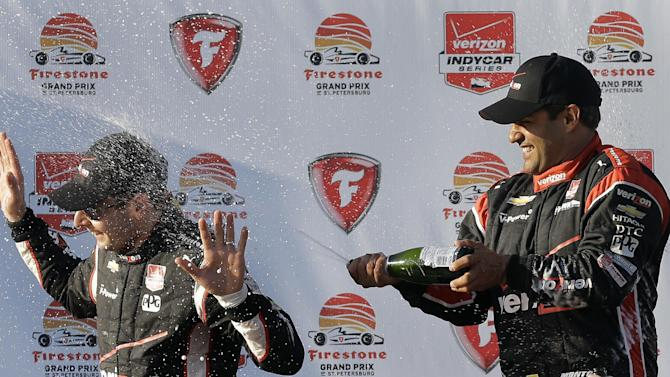 Race winner Juan Pablo Montoya, right, of Colombia, sprays champagne on runner-up Will Power, of Australia, after the IndyCar Firestone Grand Prix of St. Petersburg auto race Sunday, March 29, 2015, in St. Petersburg, Fla.  (AP Photo/Chris O'Meara)