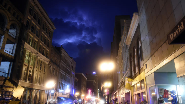 Lightning strikes behind a bank of storm clouds in Knoxville, Tenn., on Sunday, July 27, 2014. Authorities say powerful storms crossing east Tennessee have destroyed 10 homes and damaged others. (AP Photo/The Knoxville News Sentinel, Saul Young)