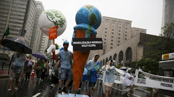 Activists push a sign of a melting ice cream in the form of the planet, during a rally held the day before the start of the Paris Climate Change Conference (COP21), in Sao Paulo