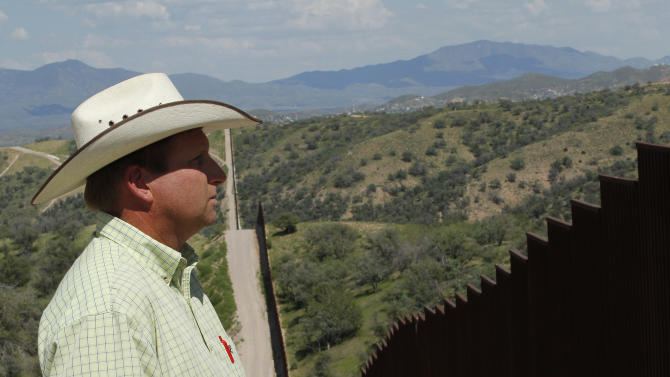 In this Friday, Aug. 10, 2012 photo, rancher Dan Bell, who leases a 35,000-acre cattle ranch along the border between the United States and Mexico, looks at the imposing border fence, in Nogales, Ariz. When Bell drives through the property, he speaks of the hurdles that the Border Patrol faces in his rolling green hills of oak and mesquite trees: The hours it takes to drive to some places, the wilderness areas that are generally off-limits to motorized vehicles, and the environmental reviews required to extend a dirt road. (AP Photo/Ross D. Franklin)