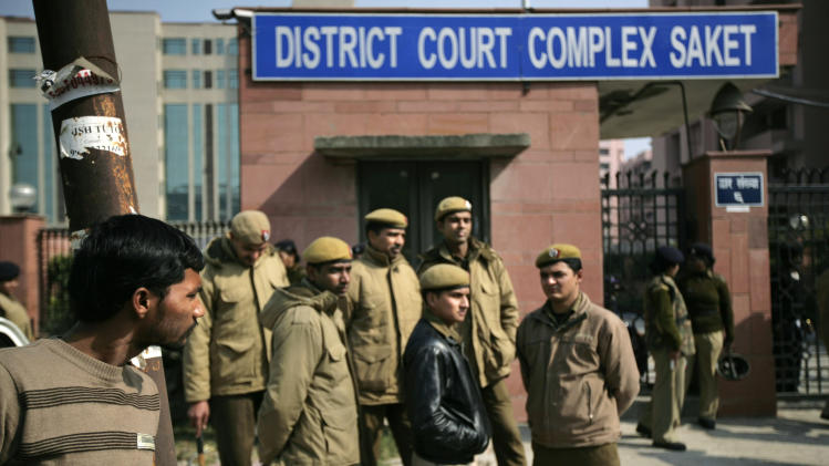 Delhi policemen stand guard near the gate of a district court where the accused in the gang rape and murder of a 23-year-old student are undergoing trial, in New Delhi, India, Thursday, Jan. 24, 2013. The trial of the five men charged began in a closed courtroom Thursday with opening arguments by the prosecution lawyers in a special fast-track court set up just weeks ago to handle sexual assault cases. (AP Photo/ Altaf Qadri)