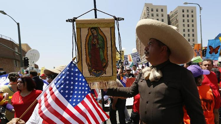 An immigrant wearing a traditional charro hat from Mexico, right, holds a banner of Mexico's Virgin of Guadalupe, as they gather to march during a May Day rally in downtown Los Angeles on Wednesday, May 1, 2013. In celebration of May Day, people have gathered across the country to rally for various topics including immigration reform. (AP Photo/Damian Dovarganes)