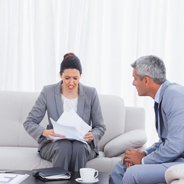 Stressed-businesswoman-holding-documents-and-businessman-trying-to-calm-her_web