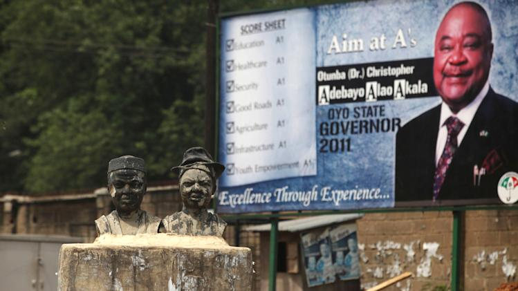 Yoruba statues  Left, are seen by a Campaign billboard of Oyo State Governor Aloa Akala in Ibadan, Nigeria, Friday, April 8, 2011, ahead of the first of three crucial elections in the oil-rich nation of Nigeria. There are some worrying signs of tampering with the ballot, like authorities in the northern Katsina state say a local politician hired thugs to steal 200 ballots after Saturday's elections and allegedly beat an official. (AP Photo/Sunday Alamba)
