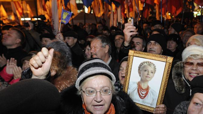 A protester holds up a photo of the imprisoned former Ukrainian Prime Minister, Yulia Tymoshenko, as supporters of the Ukrainian Opposition party take part in a rally outside the Central Elections Commission building in Kiev, Ukraine, Monday, Nov. 12, 2012. (AP Photo/Sergei Chuzavkov)