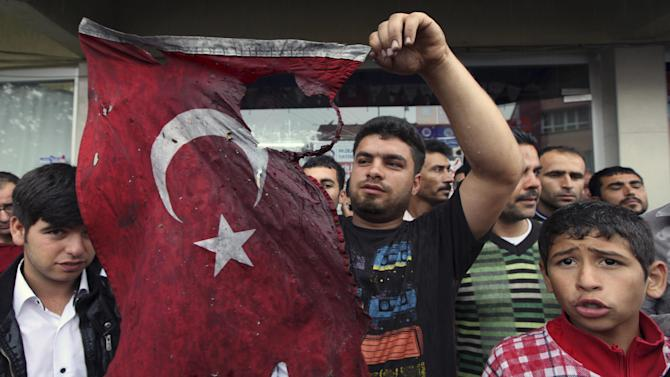 """Turkish people display a damaged national flag found in the debris of a destroyed shop as they stage an anti-government protest near the scene at one of the Saturday explosion sites that killed 46 and injured about 50 others, in Reyhanli, near Turkey's border with Syria, Monday, May 13, 2013. Prime Minister Recep Tayyip Erdogan said Monday Turkey would """"not refrain"""" from responding to twin car bombings it has blamed on Syria but also said it would also act with caution and not be drawn into its neighbor's civil war.  (AP Photo/Burhan Ozbilici)"""
