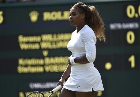 Serena Williams of the U.S. holds her stomach before retiring from her women's doubles tennis match with Venus Williams of the U.S. against Kristina Barrois of Germany and Stefanie Voegele of Swit