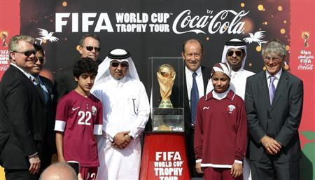 Qatar Football Association general secretary Saoud Al-Mohannadi pose with others next to the FIFA World Cup trophy following its arrival in Doha, on a tour
