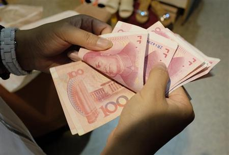 A woman counts Chinese yuan notes at a market in Beijing