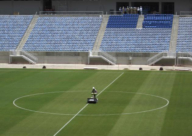 A workman rolls the grass on the pitch inside the Arena Das Dunas stadium as work continues in preparation for the 2014 FIFA World Cup soccer championship in Natal, Brazil