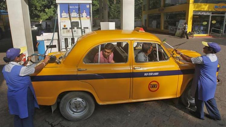 An employee fills a taxi with diesel as her colleague clean the windows of the car at a fuel station in Kolkata September 19, 2012. REUTERS/Rupak De Chowdhuri/Files