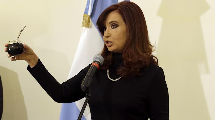 Argentine President Cristina Fernandez shows a mate gourd, during a news conference in Rome, Monday, March 18, 2013. Pope Francis' diplomatic skills were put to the test Monday as he had lunch with Argentine President Cristina Fernandez: As leader of Argentina's Catholics, he had accused her populist government of demagoguery while she called his position on gay adoptions reminiscent of the Middle Ages and the Inquisition. That was then. On Monday, Fernandez gave the new pope a mate gourd and straw, to hold the traditional Argentine tea that Francis loves, and he gave her a kiss. (AP Photo/Gregorio Borgia)