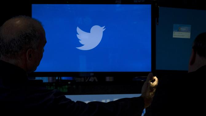 File picture shows an employee adjusting a screen that displays the Twitter logo ahead of the company's IPO on the floor of the New York Stock Exchange