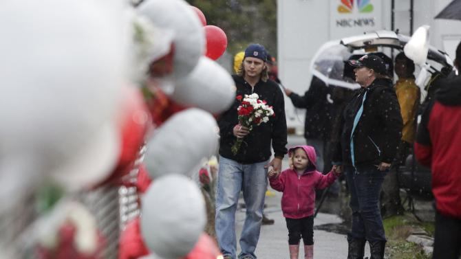 Chris Green and Angela Green, both graduates of Marysville-Pilchuck High School, walk with their daughter Dorothy as they take flowers to the makeshift memorial outside the school, in Marysville