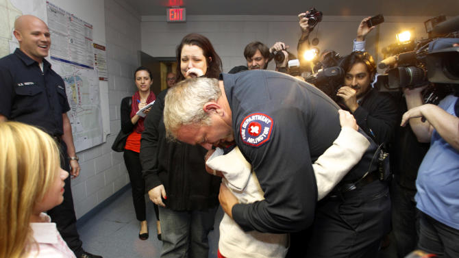 Rebecca Quintanilla, center left, wipes tears from her face as her adopted son Koregan, 10, hugs Arlington Fire Fighter Wesley Keck, center right, as the two meet Thursday, Nov. 15, 2012, in Arlington, Texas. A Texas boy abandoned at a fire station as an infant got his wish for his 10th birthday: to meet the firefighter who saved him. On Thursday evening, the boy was to celebrate his recent birthday by meeting Arlington firefighter Wesley Keck, riding on a fire truck and touring the station. (AP Photo/Tony Gutierrez)