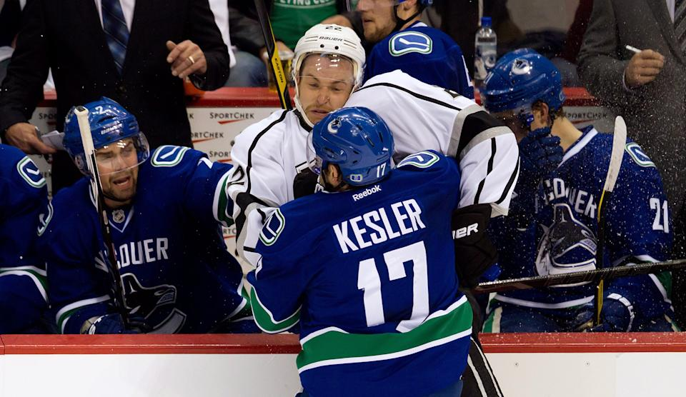 Vancouver Canucks' Ryan Kesler, 17, checks Los Angeles Kings' Trevor Lewis during the second period of game 5 of an NHL Western Conference quarterfinal Stanley Cup playoff hockey series in Vancouver, British Columbia on Sunday April 22, 2012. (AP Photo/The Canadian Press, Darryl Dyck)