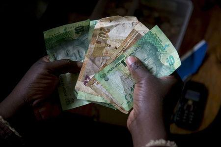 A shopkeeper counts out change above her cash box at her shop in Hillcrest, west of Durban