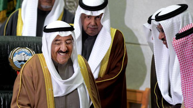 """The Amir of Kuwait, Sheikh Sabah Al Sabah, left, receives a copy of a speech given by Kuwait's Prime Minister, Sheikh Jaber al-Mubarak al-Sabah, second right, during the inauguration of the 14th Legislative Term of the National Assembly in Kuwait, Sunda,  Dec 16, 2012. Security forces blocked hundreds of protesters from staging a rally outside the parliament building Sunday, as Kuwait's amir denounced anti-government factions as committing """"treason"""" and vowed to stand firm amid the country's deepening political crisis. (AP Photo/Gustavo Ferrari)"""