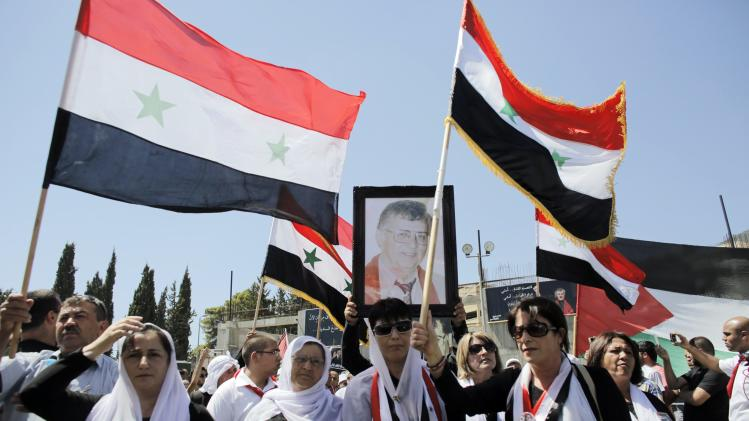 Mourners from Druze community in Majdal Shams carry Syrian national flags as another mourner carries a portrait of Palestinian Druze poet Samih al-Qasim during his funeral in Rameh