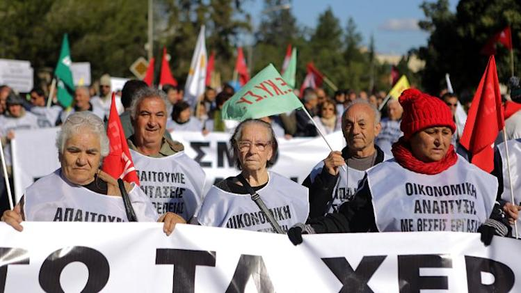 Cypriot left-wing party supporters march in the capital Nicosia, on December 14, 2013, as they protest againt the the privatisation of state utilities and government economic policy