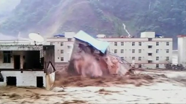 A video still shows a building collapsing amid floodwaters caused by torrential rain in Deyang City