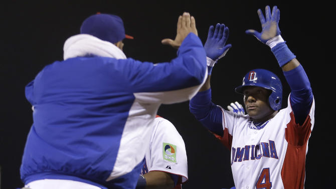 The Dominican Republic's Miguel Tejada (4) celebrates after scoring against the Netherlands during the fifth inning of a semifinal game of the World Baseball Classic in San Francisco, Monday, March 18, 2013. (AP Photo/Ben Margot)