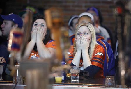 File photo of Broncos fans reacting to a turnover as they watch their team's NFL Super Bowl XLVIII against the Seahawks in Denver