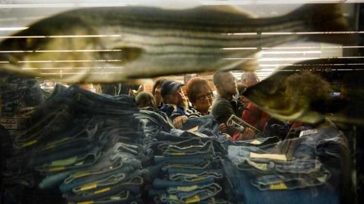 "Shoppers pick through stacks of discounted jeans beside a giant aquarium inside Bass Pro Shops after the doors opened at 5 a.m., kicking off ""Black Friday"" and the holiday shopping season in Memphis, Tenn. Friday Nov. 23, 2112.. Some bargain-hunters waited outside the store for four and a half hours in the rain for the chance to be first in line. For the first time many retailers opened as early as 8 p.m. on Thursday sparking some criticism for shortening their employees' Thanksgiving holiday. (AP Photo, Brandon Dill, Commercial Appeal)"