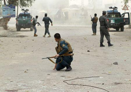 Policemen keep watch at a site after a third explosion in Jalalabad