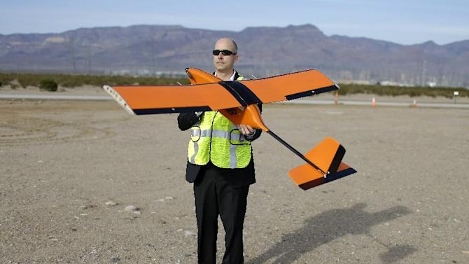 FILE - In this Dec. 19, 2014, file photo, Dan Johnson of Sensurion Aerospace holds the Sensurion Aerospace Magpie commercial drone during an event near Boulder City, Nev. The Obama administration is on the verge of proposing long-awaited rules for commercial drone operations in U.S. skies, but key decisions on how much access to grant drones are likely to come from Congress next year. (AP Photo/John Locher, File)
