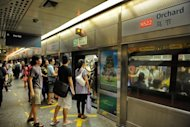 File photo shows commuters boarding a train at the Orchard subway station in Singapore. Singapore's metro system has been plagued by outdated equipment and poor maintenance for years, according to a high-level inquiry that criticised the network's operator for chasing profits